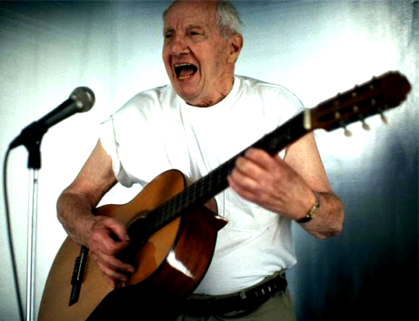 Elderly Man Singing with Guitar